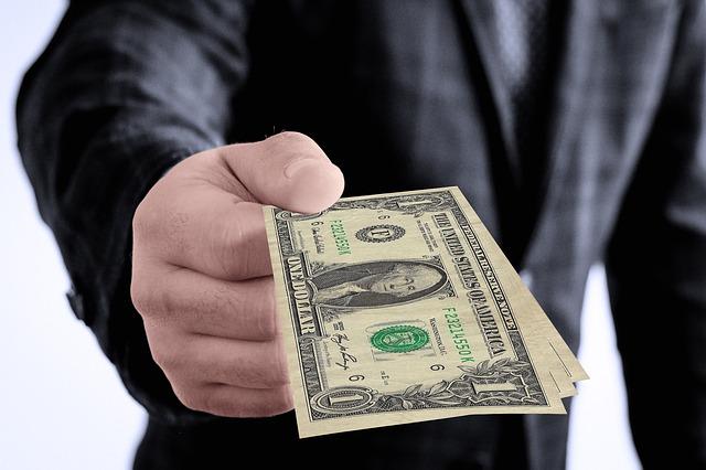 muž podávající peníze